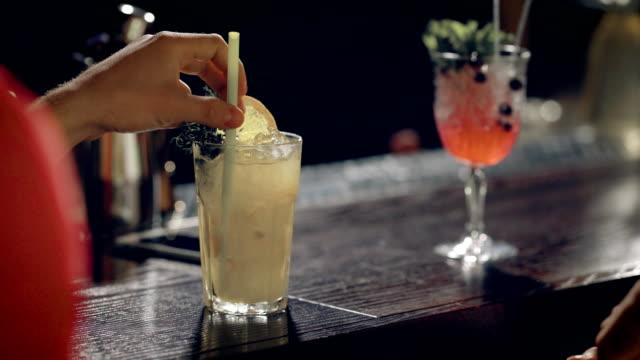 close-up tiro de um copo com uma bebida alcoólica que fica na barra, mão de um homem se transforma um tubo dentro de um coquetel - vídeo