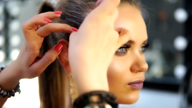 Close up shot of a makeup artist's hands applying golden shiny pieces of metallic paper on a model's face. Preparing for the fashion show. Dressing room for models video