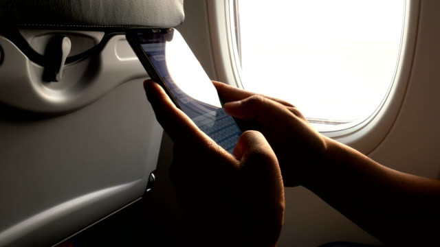 4K Close up shot of a male passenger on an airplane is chatting with friends via smartphone.
