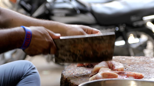 A close up shot of a man choping raw chicken into pieces in a roadside stall in India video