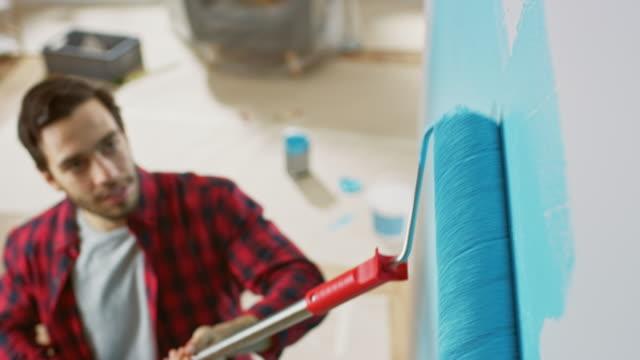nära upp skott av en man i bruna jeans och röd rutig skjorta måla en vägg med en roller. lacken är ljusblå. rum renoveringar hemma. skott från ovan. - painting wall bildbanksvideor och videomaterial från bakom kulisserna