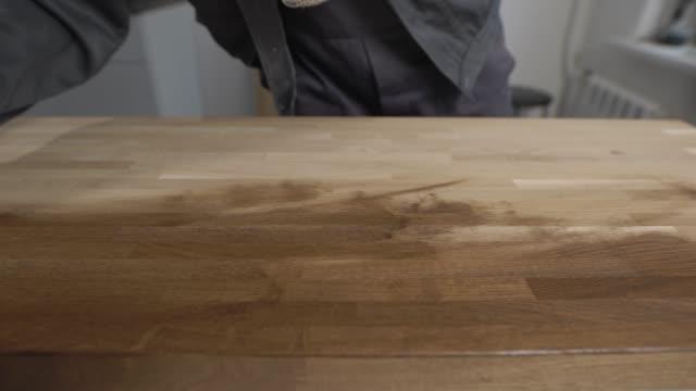 nära upp skott av en man som bär skyddshandskar som arbetar med en trä - construction workwear floor bildbanksvideor och videomaterial från bakom kulisserna
