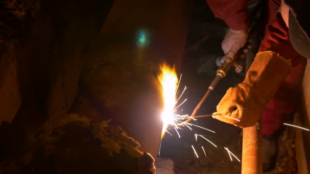 Close up shot of a man welding a heating system pipe at night video