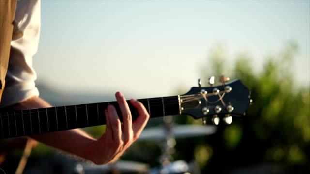 nära upp skott av en mans händer, som spelar gitarren med en medlare - akustisk gitarr bildbanksvideor och videomaterial från bakom kulisserna