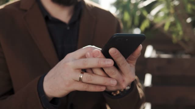 close up shot of a man's hands who prints text sms on a mobile phone