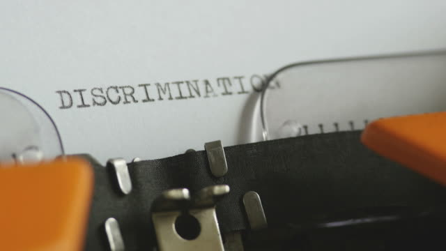 Close up shot of a person writing DISCRIMINATION on an old typewriter, with sound...