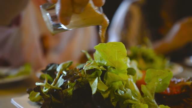schuss einen teller mit frischen grünen salat während asiatische frau gießen sauce hautnah und das vegetarische essen im restaurant zu essen. gesunde ernährung und diät-konzept. - portion stock-videos und b-roll-filmmaterial