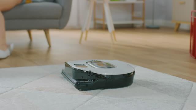 bir halıdan toz emme akıllı robot elektrikli süpürge shot yakın. güzel çift bir kanepe üzerinde oturuyor ve arka planda konuşuyor. teknolojik ev aletleri cihaz onları geçmiş taşır. - ev temizleme stok videoları ve detay görüntü çekimi