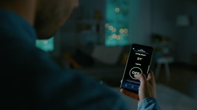 アクティブスマートホームアプリケーションとスマートフォンのクローズアップショット。人が画面をタップしていると、部屋の中で光がオンにされています。それはアパートで居心地のよ� - 文字記号点の映像素材/bロール