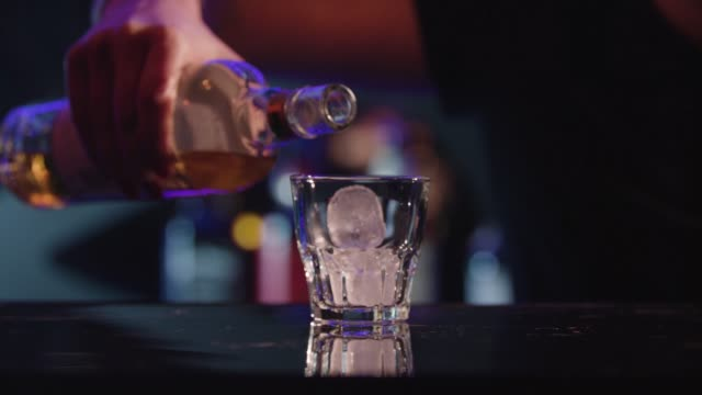 close up shot of a tumbler glass with whiskey on the rocks. whisky is poured over ice cubes - scotch whisky video stock e b–roll