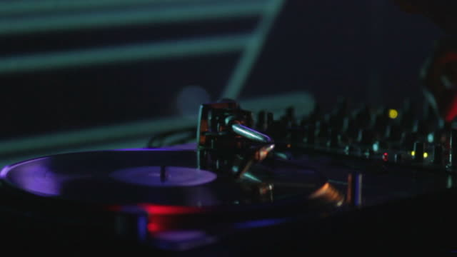 Close up shot of a vinyl rotating and a DJ mixing music on his audio device video