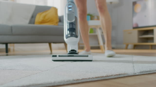 close up shot of a young beautiful woman in jeans shirt and shorts vacuum cleaning a carpet in a bright cozy room at home. she uses a modern cordless vacuum. she's happy and cheerful. - moquette video stock e b–roll