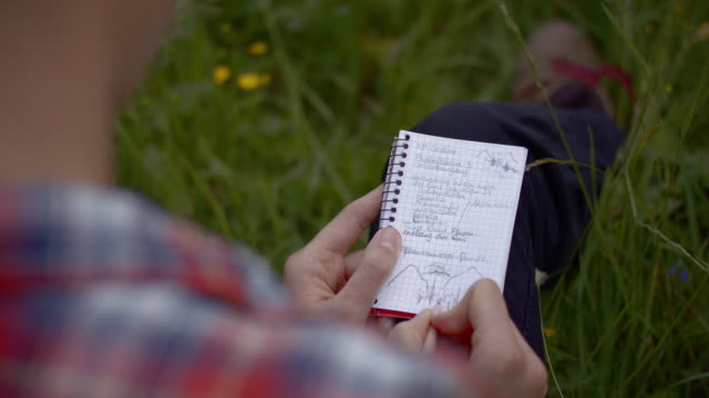 close up shot of a young woman writing on a notepad - эскапизм стоковые видео и кадры b-roll