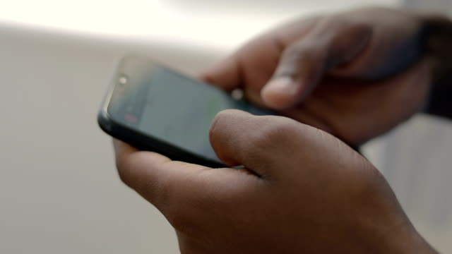 Close up shot of african american student using smartphone.