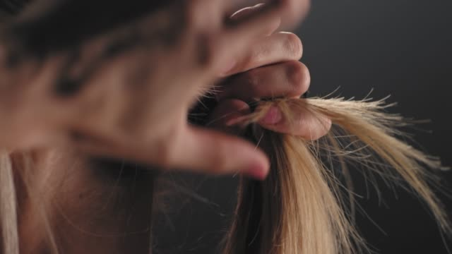 stockvideo's en b-roll-footage met close-up shot van een atletische kaukasische vrouw koppelverkoop haar in een paardenstaart op een mistige donkere achtergrond - paardenstaart haar naar achteren