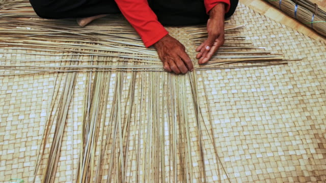 Close up shot of an expert old female hands weaving mat in Terengganu, Malaysia.