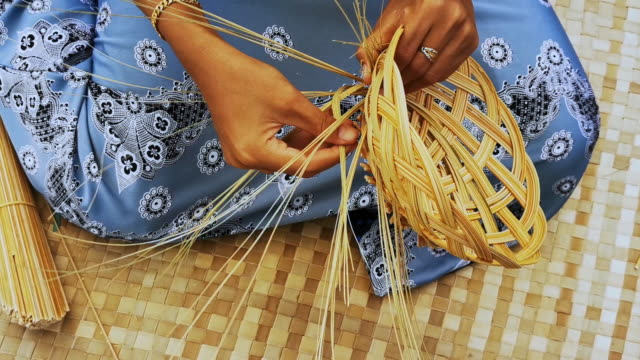 Close up shot of an expert young female hands weaving rattan basket in Terengganu, Malaysia.