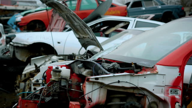 Close up shot of broken and torn apart cars lying on junkyard for recycling video