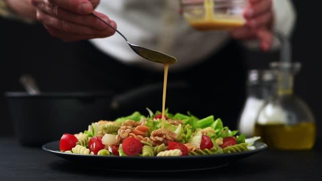 파스타와 샐러드 접시에 겨자 소스를 확산 요리사의 닫기 샷 - 식초 스톡 비디오 및 b-롤 화면