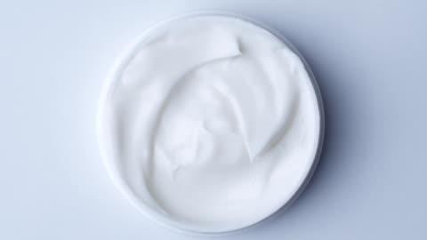 vidéos et rushes de fermez-vous vers le haut du plan de crème de cosmétiques avec rotation, vue supérieure - marchandise