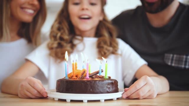 närbild skott av dotter blåser ut ljusen på födelsedagstårta under online-fest, slow motion - birthday celebration looking at phone children bildbanksvideor och videomaterial från bakom kulisserna