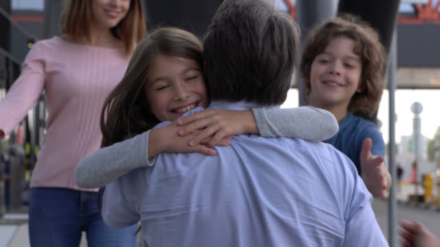 vídeos de stock e filmes b-roll de close up shot of excited family hugging picking daddy up at the airport - abraçar