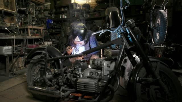 närbild skott av erfaren man som arbetar i skräddarsydda motorcykel verkstad - mekaniker bildbanksvideor och videomaterial från bakom kulisserna