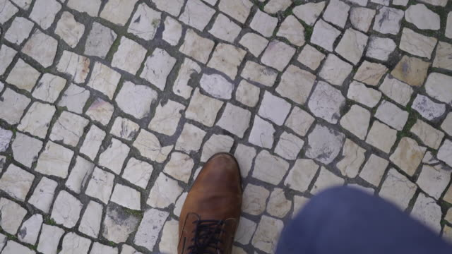 vídeos de stock e filmes b-roll de close up shot of feet walking along a stone road - people lisbon