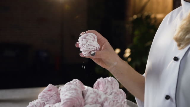 Close up shot of female baker hands taking marshmallow from the plate