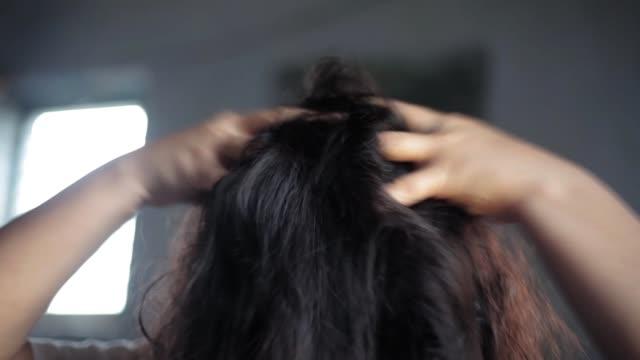 茶色の髪をした女性のクローズアップショットは、ぼやけた背景を持つ彼女の手でそれらをマッサージします。 - ダメージ点の映像素材/bロール