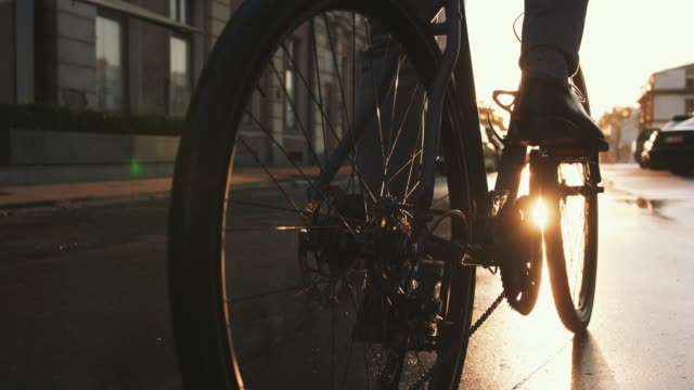 close up shot of handsome young man driving his bicycle on the street in city center during sunrise, slow motion - veicolo a due ruote video stock e b–roll