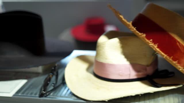 vidéos et rushes de fermez-vous vers le haut du projectile des chapeaux se reposant sur une étagère dans un magasin de vêtement - chapeau