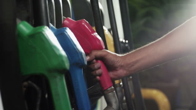 Close up shot of insertion of the nozzle and pumping gasoline Close up shot of insertion of the nozzle and pumping gasoline into a white vehicle at the gas station. refueling stock videos & royalty-free footage