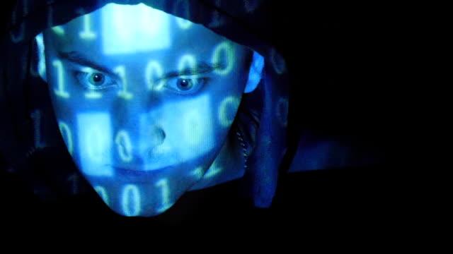 クローズアップショットの男性の顔のハッカー、バイナリーコード予測します。ソースコード凸形を攻撃、怒っている男性の顔、黒の背景ます。 ビデオ