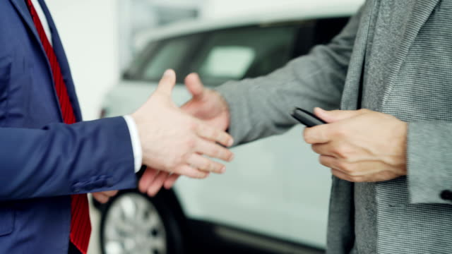 Close up shot of male hands getting car keys after successful deal with sales manager and shaking hands. Buying and selling autos, businessmen and handshake concept. Close up shot of male hands getting car keys after successful deal with sales manager and shaking hands in dealership. Buying and selling autos, businessmen and handshake concept. car salesperson stock videos & royalty-free footage