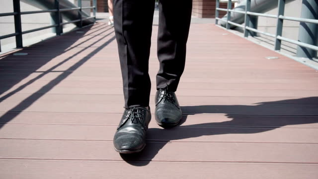 Close up shot of male legs in black shoes walking over bridge Close up shot of male legs in black shoes walking over bridge. White female shoes in background. Leisure walk to office concept stepping stock videos & royalty-free footage