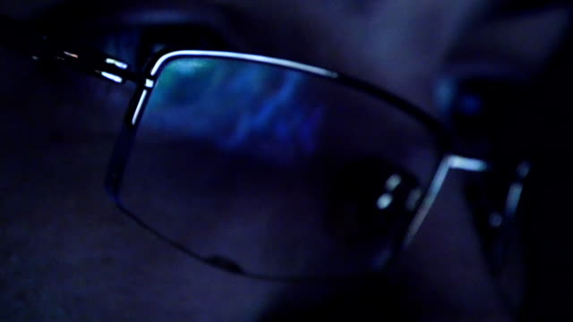 Close up shot of man in glasses surfing internet at night video