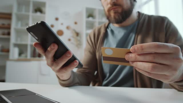 close up shot of man shopping online via app on smartphone - credit card filmów i materiałów b-roll