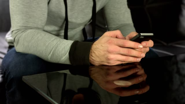 Close up shot of man's hands using a smart phone at home video