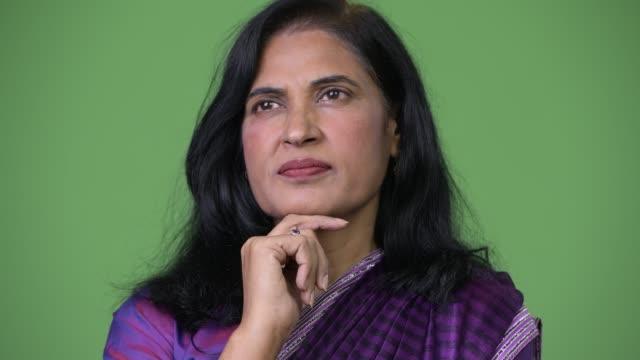 close up shot of mature beautiful indian woman thinking while wearing sari traditional clothes - sari filmów i materiałów b-roll