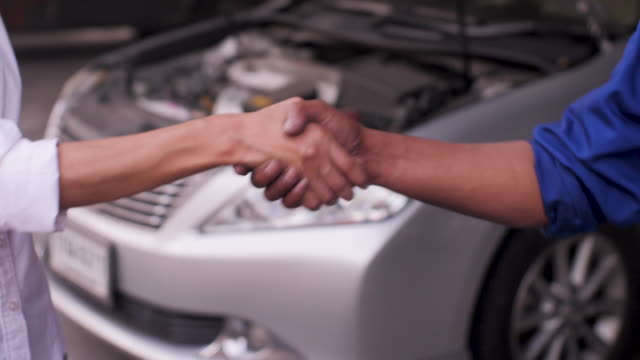Close Up shot of mechanic and customer shaking hands in an auto repair shop, car service concept video