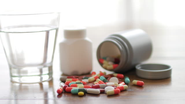 close up shot of medicine capsule with wooden table background with drinking water , dolly shot right to left movement - antibiotico video stock e b–roll