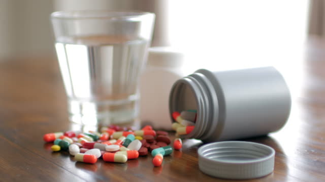 Close up shot of medicine capsule with wooden table background with drinking water video