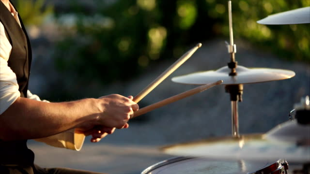 close up shot of men's hands, who plays the drums, he holds the wand in his hand close up shot of the men's hands, who holds the drumsticks in their hand, the people energetically hit them on the plates in the daytime outside, maybe this is a street musician classical concert stock videos & royalty-free footage