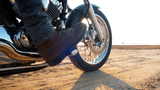 Close up shot of motorcyclist driving his motorbike on the road during sunset