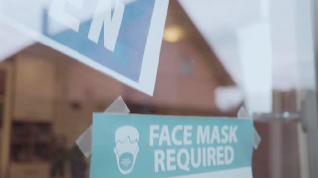 vídeos de stock, filmes e b-roll de close-up tiro de nota máscara facial necessária na porta - sinal