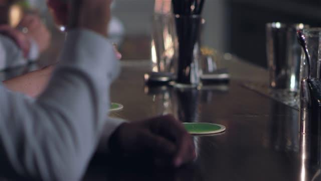 vídeos de stock, filmes e b-roll de close-up tiro de pessoas pegando e colocando para baixo suas bebidas alcoólicas em um bar - costumer
