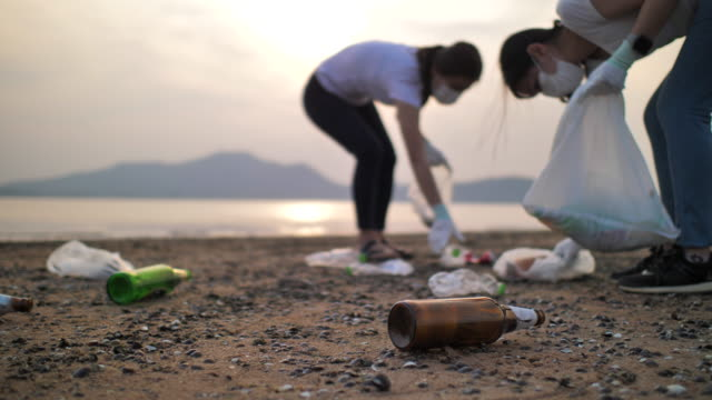 Close up shot of people picking up plastic bottles on the beach, slow motion, environment Conservation
