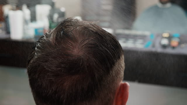 Close up shot of spraying water on head of client