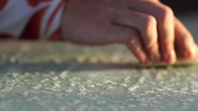 Close up shot of surfer girl waxing surfboard on beach